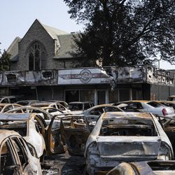 People walk past a used car lot that was burned in downtown Kenosha during unrest overnight after police shot a Black man, Jacob Blake, in the the 2800 block of 40th Street, Monday morning, Aug. 24, 2020.