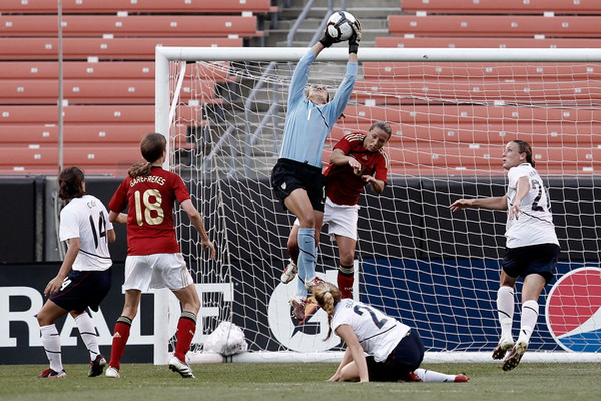 CLEVELAND - MAY 22:  Hope Solo #1 of the United States makes a save in front of Inka Grings #8 of Germany during the game on May 22, 2010 at Browns Stadium in Cleveland, Ohio.  (Photo by Jared Wickerham/Getty Images)