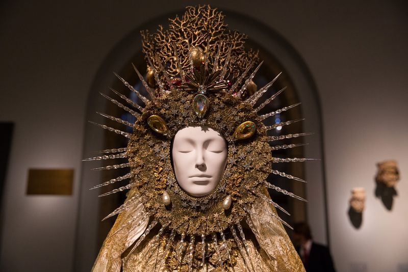 A mannequin wears an elaborate headdress.