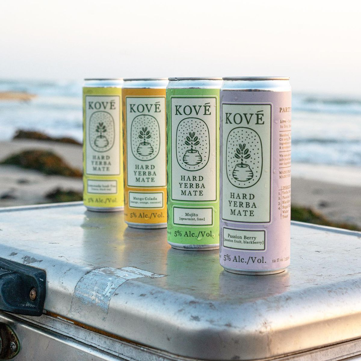 Four cans of Kove Hard Yerba Mate on a cooler at the beach