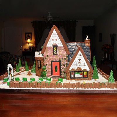 A gingerbread house with a gingerbread fence surrounding it.
