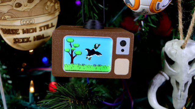 A close shot of TV Christmas ornament hanging on a green Christmas tree. Duck Hunt is on the screen.