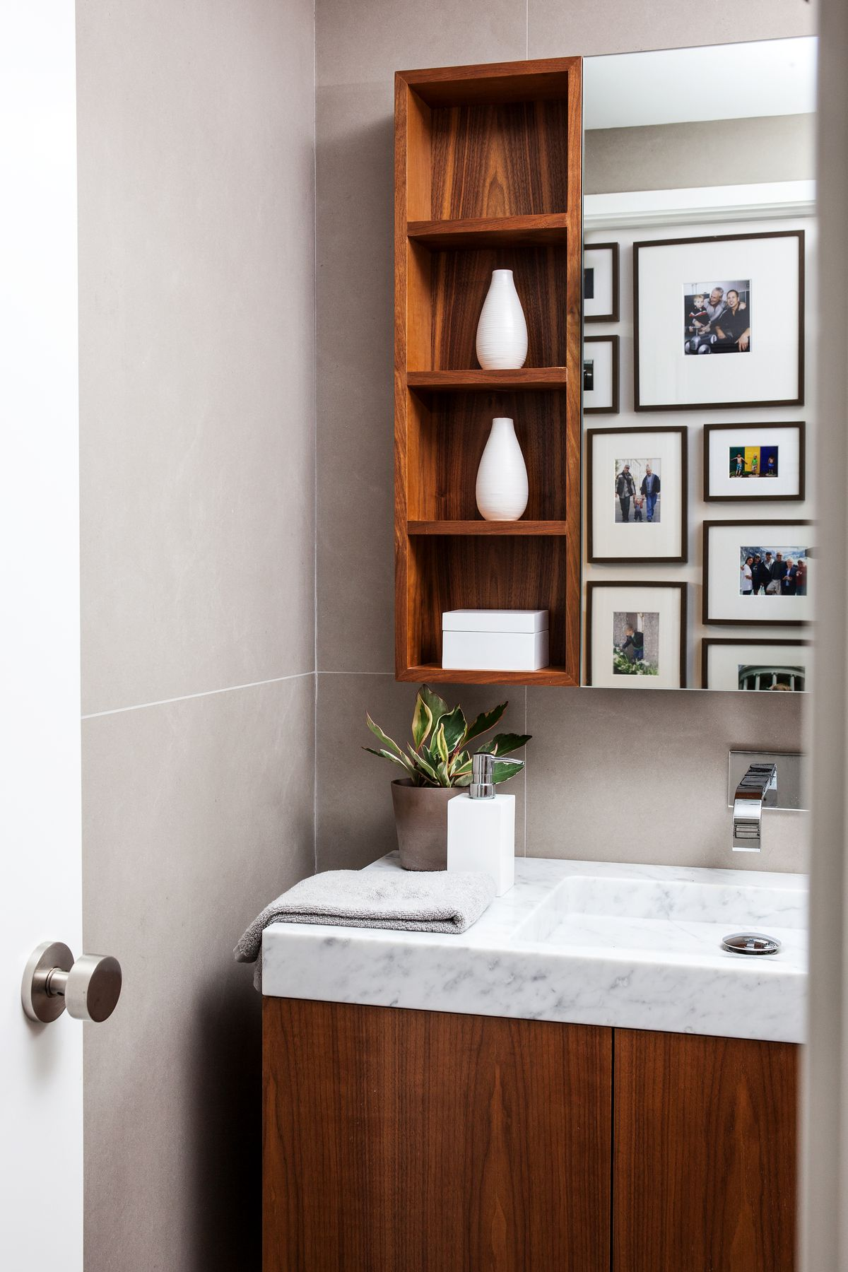 In the bathroom, there's a walnut vanity with marble sink. A mirror and walnut shelves hang above it.