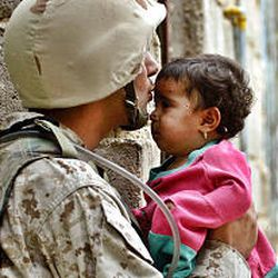 An Iraqi soldier serving with the U.S. Marines as a translator kisses a local child before he joins a foot patrol Saturday outside Fallujah, Iraq.