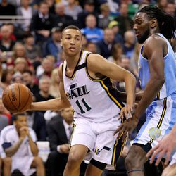 Utah Jazz guard Dante Exum (11) passes around Denver Nuggets forward Kenneth Faried (35) as the Utah Jazz and the Denver Nuggets play Wednesday, April 1, 2015, at EnergySolutions arena in Salt Lake City.