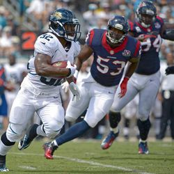 Jacksonville Jaguars running back Maurice Jones-Drew (32) makes a move to get around Houston Texans inside linebacker Bradie James (53) and defensive end Antonio Smith (94) during the first half of an NFL football game on Sunday, Sept. 16, 2012, in Jacksonville, Fla.