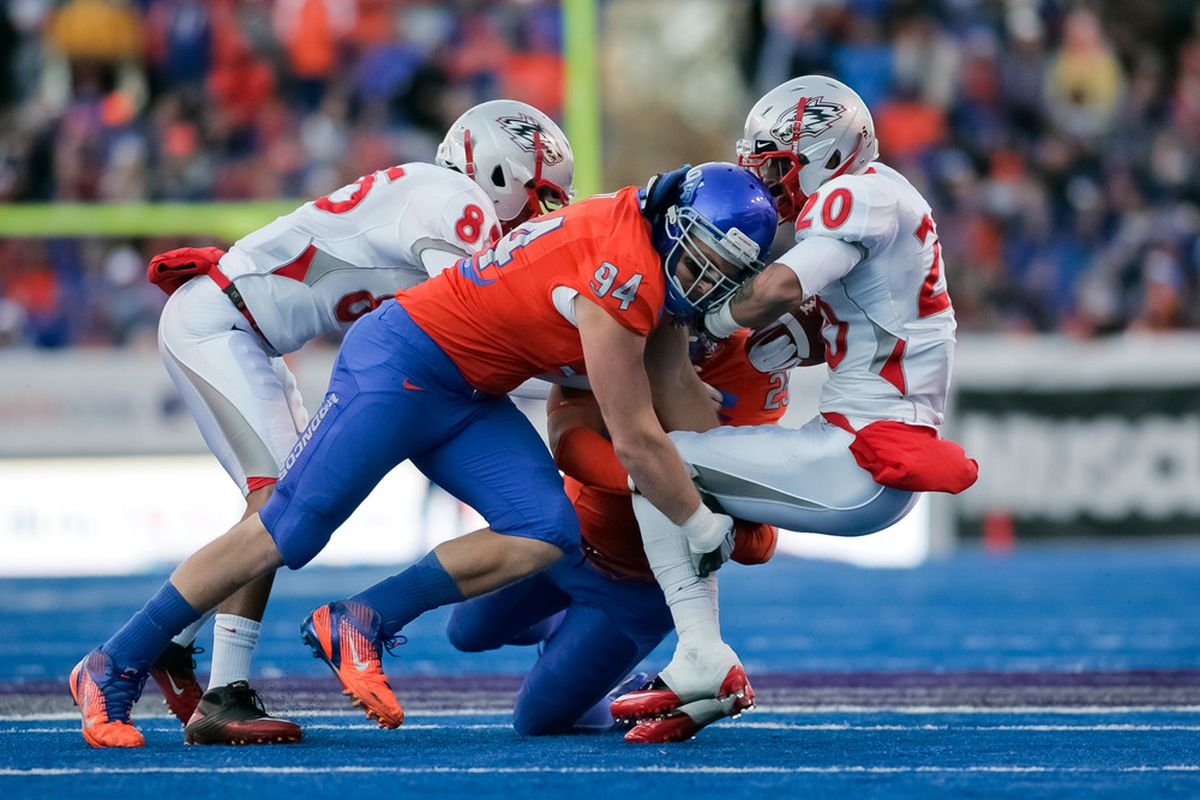 BOISE, ID - DECEMBER 03: Byron Hout #94 of the Boise State Broncos takes down Deon Long #20 of the New Mexico Lobos at Bronco Stadium on December 3, 2011 in Boise, Idaho.  (Photo by Otto Kitsinger III/Getty Images)
