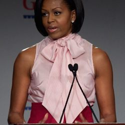 """<span class=""""credit"""">Image via Getty</span>2010: Michelle Obama wears one of her designs to address the Grocery Manufacturers Association."""