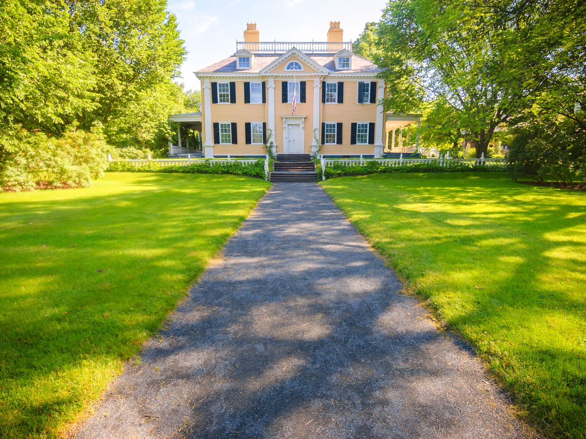 A stately two-story mansion at the end of a long walkway and lawn.