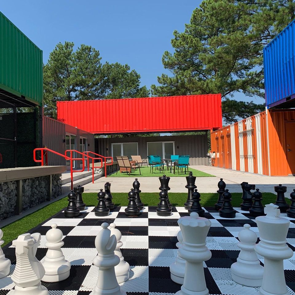 A stack of shipping containers in red, blue, and green with oversized chess in front.
