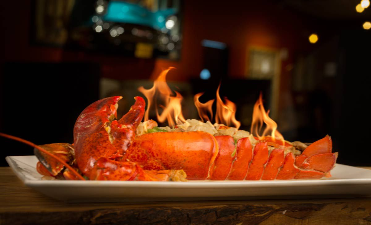 A whole lobster sits on a white plate. Flames are coming off of it.