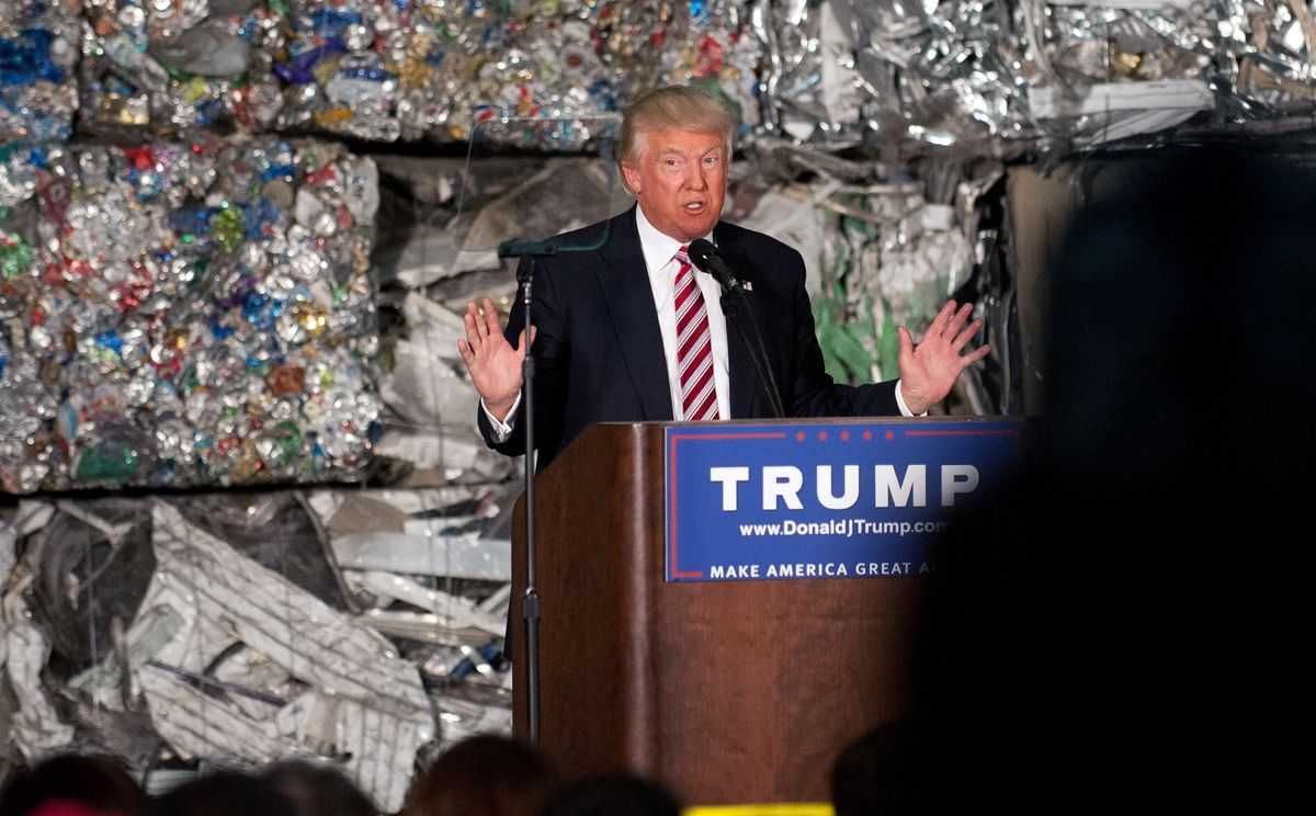 Trump in front of a wall of aluminum cans