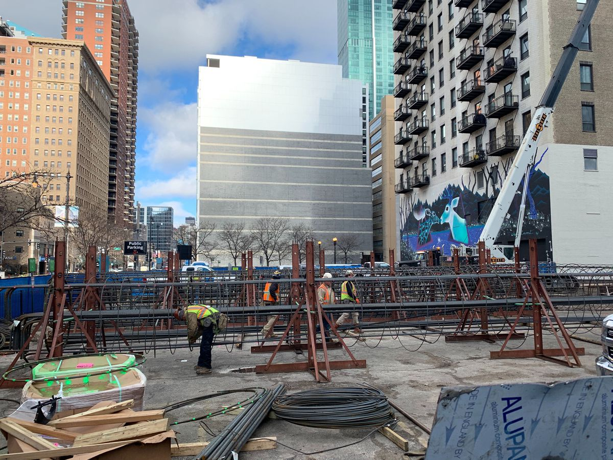 Crews working to assembling metal rebar cages that will combine with concrete to form underground foundation piers.