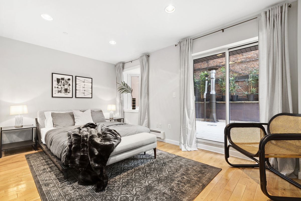 A bedroom with a large bed, hardwood floors, a rug, light grey walls, and a door that leads to a terrace.