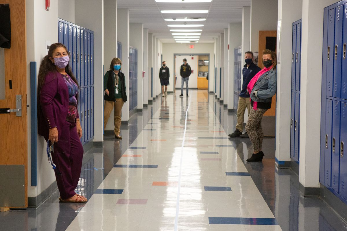 Masked teachers stand next to room doors in a long school hallway.