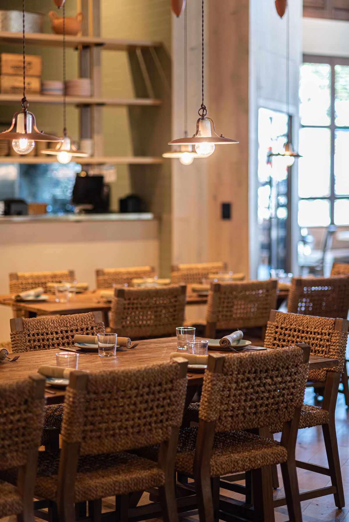 Wicker chairs inside a new restaurant with pendant lights.