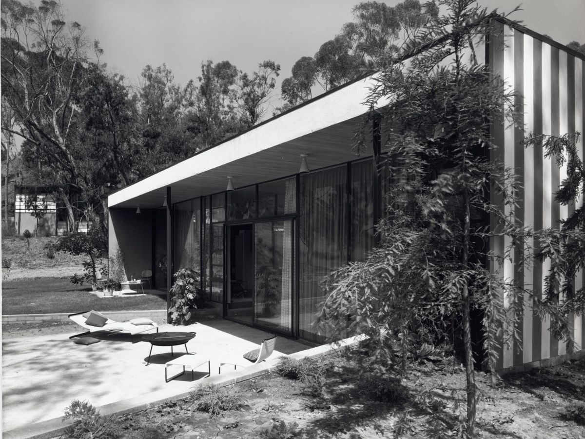 The Entenza House exterior. The roof is flat and the exterior has floor to ceiling windows. There are trees surrounding the house. There is an outdoor seating area.