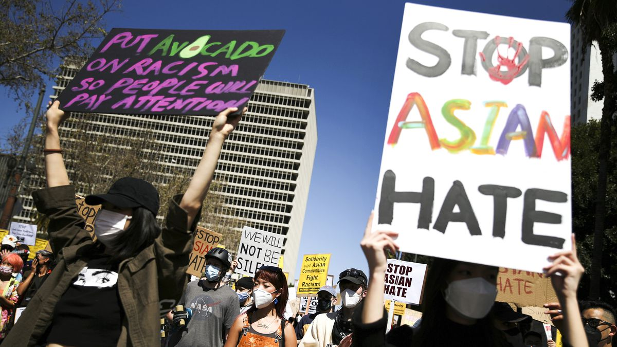 """Protesters march down a city street and carry signs, one that reads, """"Stop Asian hate,"""" and the other, """"Put avocado on racism so people will pay attention."""""""
