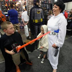 Harper Brace, as Darth Vader, points his lightsaber at his mother, Heather Brace, as Princess Leia, and brother Collier Brace, as Yoda, at Comic Con at the Salt Palace Convention Center in Salt Lake City on Saturday, Sept. 7, 2013.
