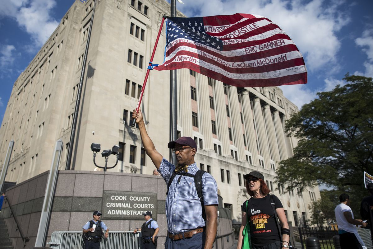 A small group of protesters march and chant outside the Leighton Criminal Courthouse as opening statements in the Chicago Police Officer Jason Van Dyke murder trial were scheduled to begin, Monday morning, Sept. 17, 2018. | Ashlee Rezin/Sun-Times
