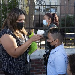 Lisa Hromoko, tech lead and an academic interventionalist, screens the temperature for second grader Jordi Olivo.