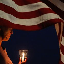 Tammy Merryweather holds a candle as she attends a vigil to honor the life and service of Marine Staff Sgt. Taylor Hoover, one of the 13 U.S. service members killed by the terrorist attack at Hamid Karzai International Airport in Kabul, Afghanistan, on Sunday, Aug. 29, 2021, at the Capitol in Salt Lake City.