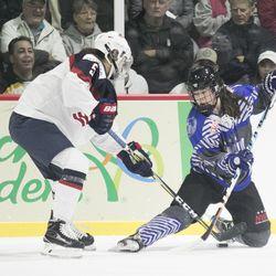Team USA defender Megan Keller and Team NWHL forward Kelly Babstock battle for the puck during a game in Wesley Chapel, FL