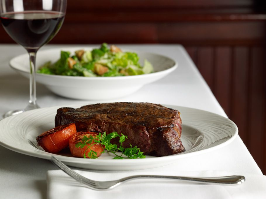 A thick cut of beef sits on a plate in the foreground with a salad in the background and a glass of red wine standing by
