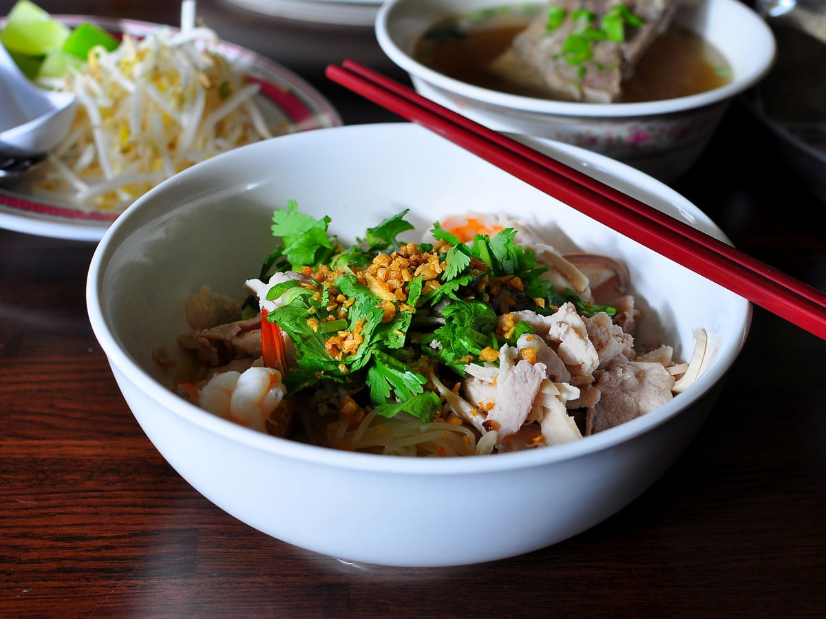 A bowl of noodle soup with broth and garnishes in the background.