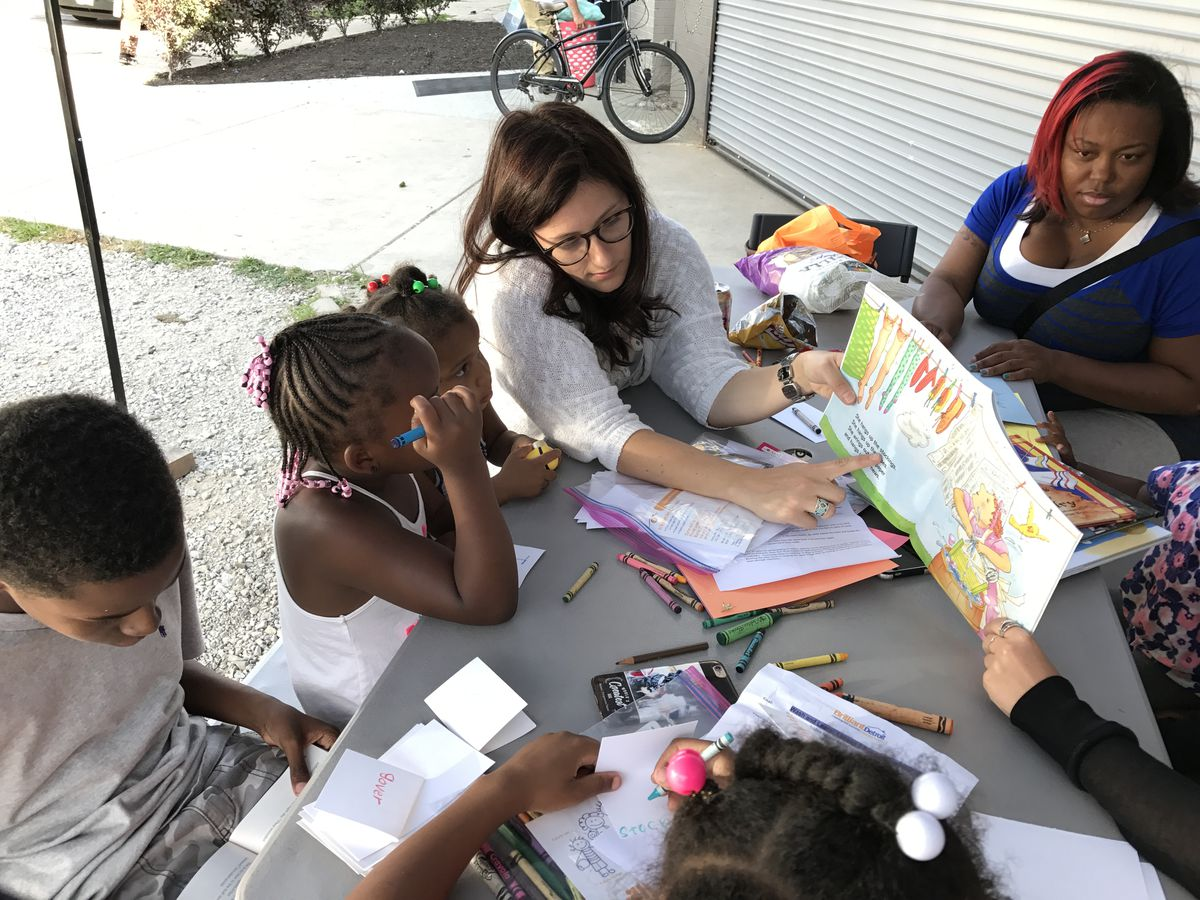 Stacy Lorne of Libraries Without Borders reads a book with children at the Fit and Fold laundromat in Detroit.