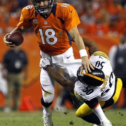 Denver Broncos quarterback Peyton Manning (18) is wrapped up by Pittsburgh Steelers linebacker Larry Foote (50) during the second quarter of an NFL football game, Sunday, Sept. 9, 2012, in Denver.
