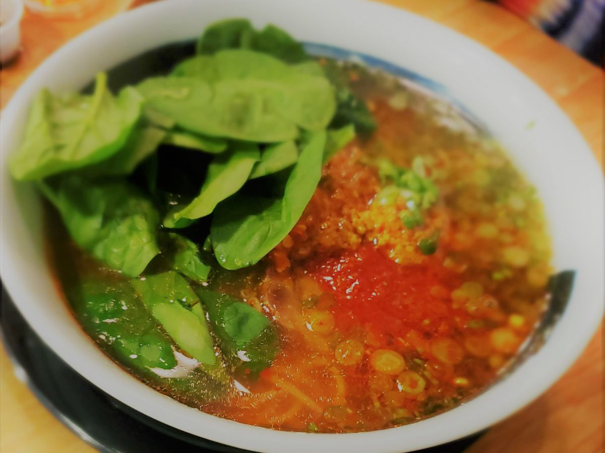 A bowl of broth with chilies and spinach