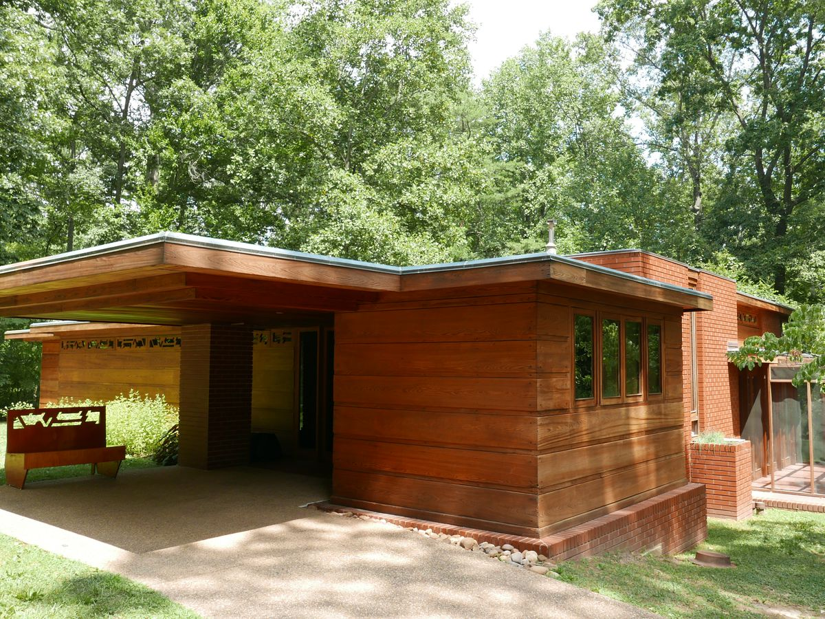 Pope-Leighey House by Frank Lloyd Wright. The facade is wood and red brick. The roof is flat. There are trees in the background.
