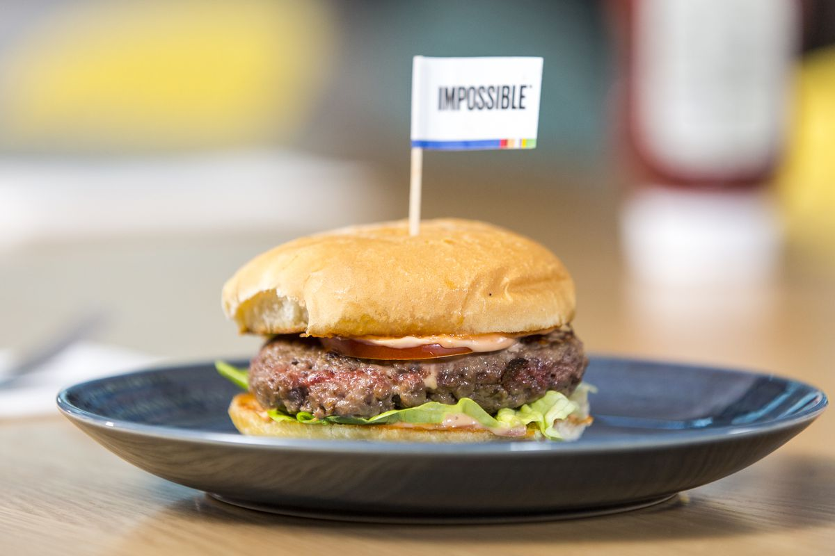 """Burger on a plate with an """"Impossible"""" flag in it."""