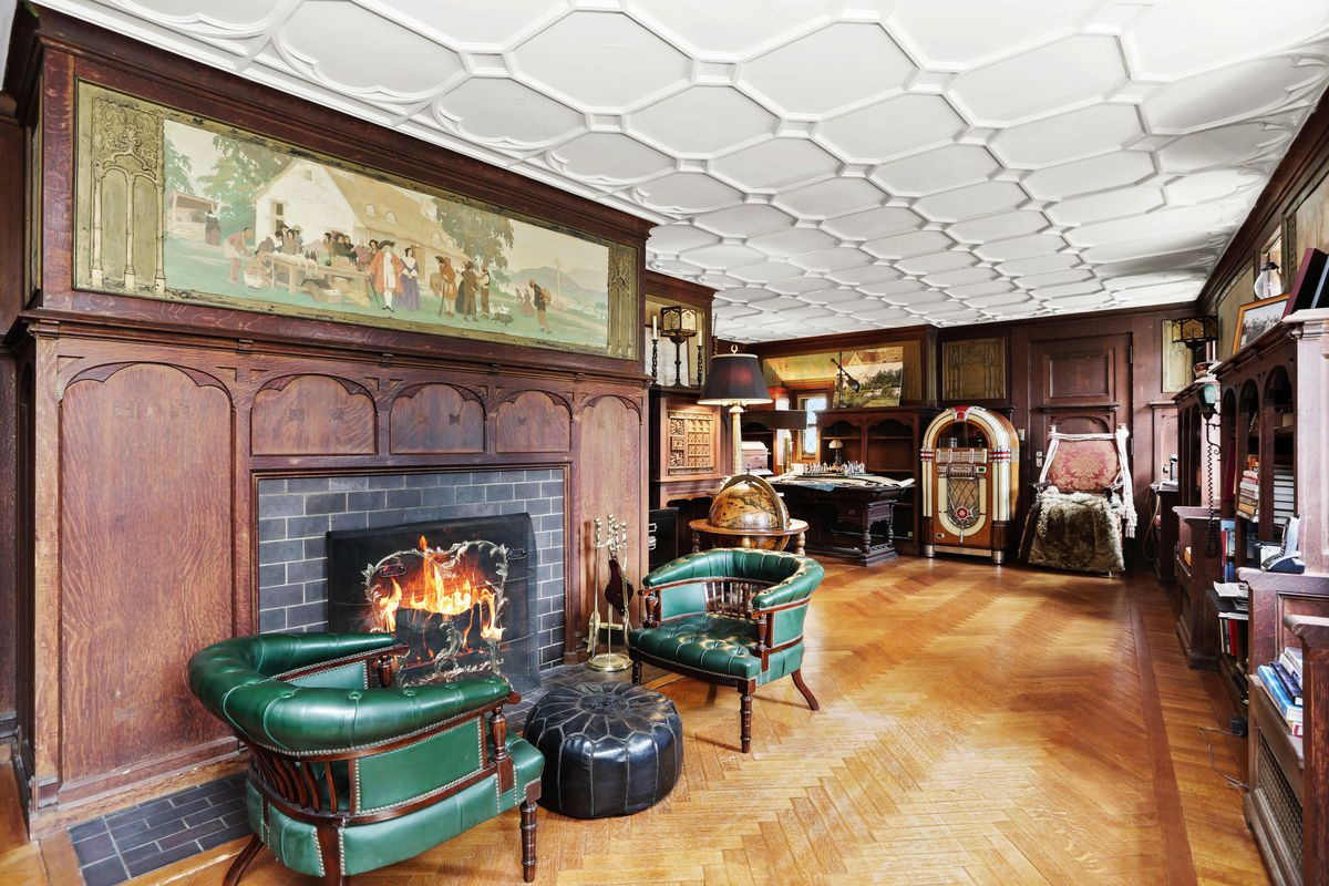 A library has a fireplace with murals above, green chairs, and bookcases.