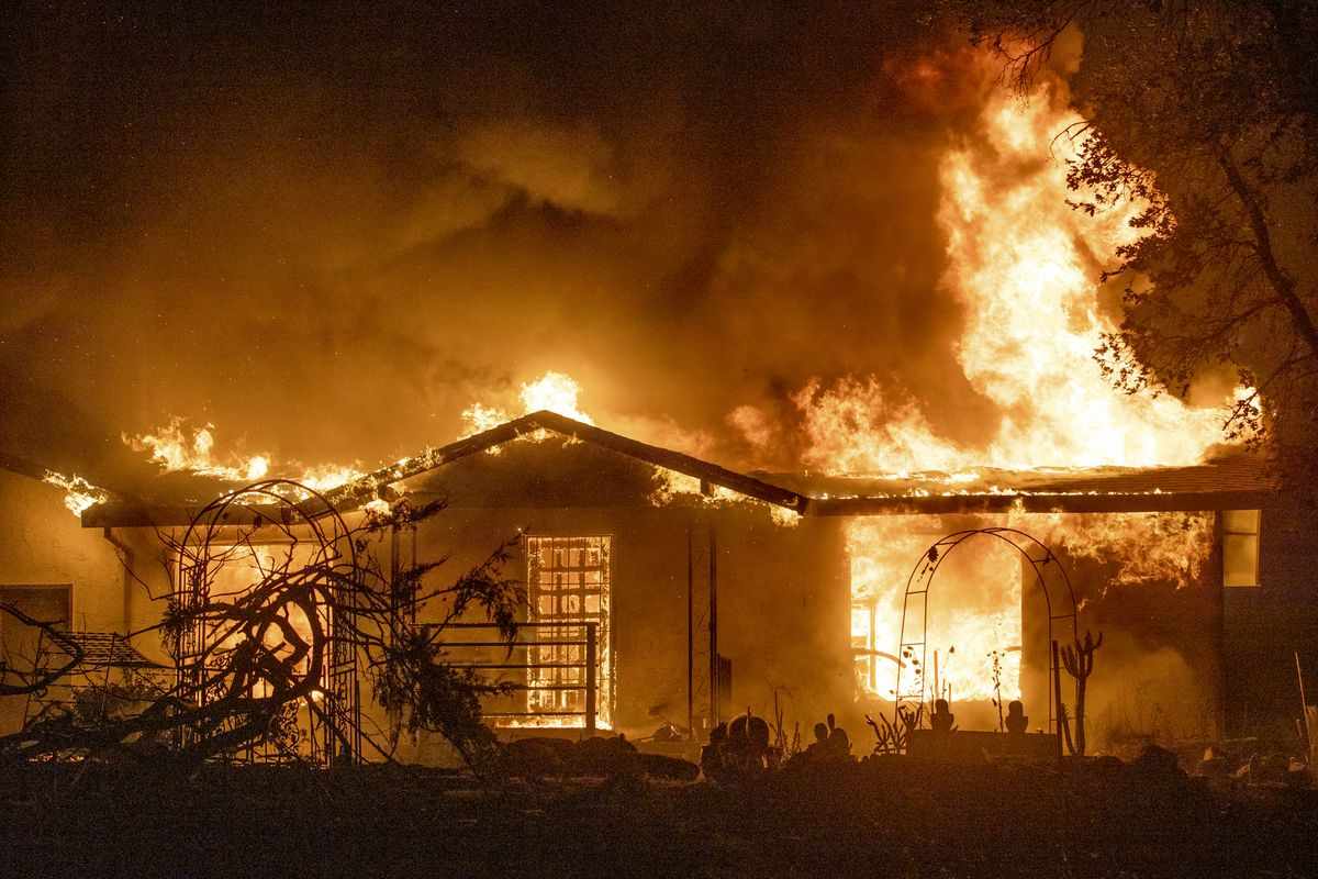 In this Sept. 27, 2020, file photo, a house burns on Platina Road at the Zogg Fire near Ono, Calif. Pacific Gas & Electric has been charged with manslaughter and other crimes, Friday, Sept. 24, 2021, in a Northern California wildfire last year that killed four people and destroyed hundreds of homes.