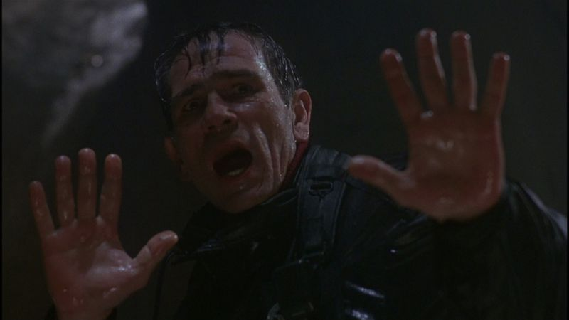 A water-soaked man raises his hands.