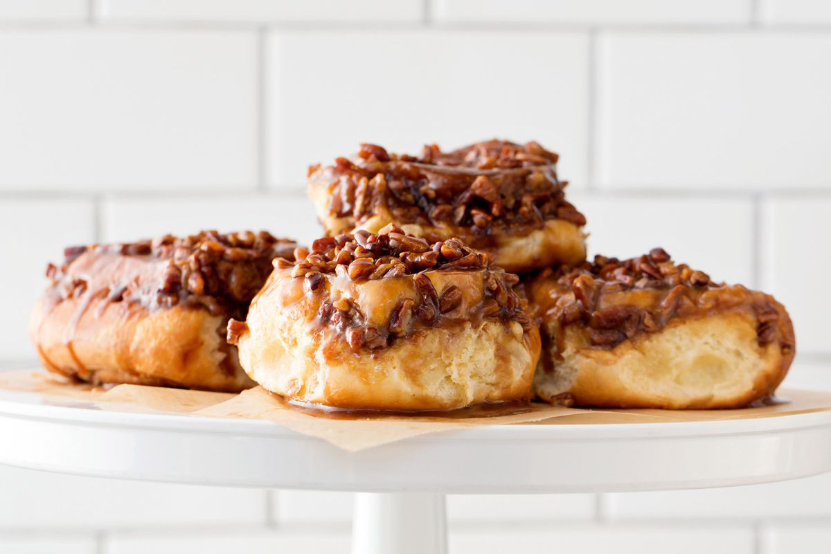 Plump sticky buns, topped with nuts, sit on a white cake display in front of a white tiled wall