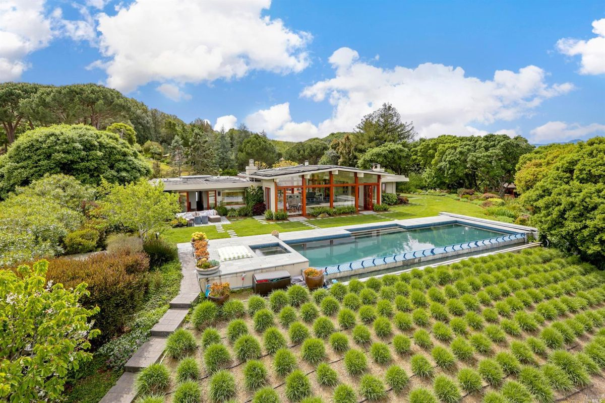 A house with a glass facade near a swimming pool and carefully landscaped vineyards in Tiburon.