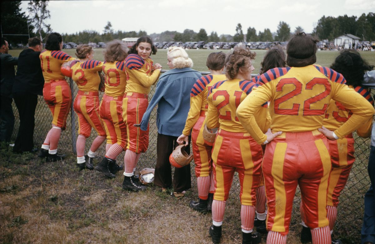 Women in orange and yellow football uniforms gather on the sidelines during a football game, circa 1940.