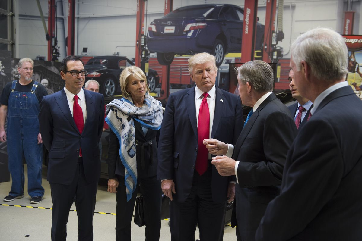 US President Donald Trump tours Snap-On Tools alongside Snap-On CEO Nick Pinchuk (2nd R), Secretary of Treasury Steve Mnuchin (L) and Secretary of Education Betsy DeVos (2nd L) in Kenosha, Wisconsin, April 18, 2017, prior to signing the Buy American, Hire American Executive Order. (Photo credit: SAUL LOEB/AFP/Getty Images)