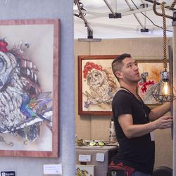 Michael Rohner adjusts framed pieces on the walls of his booth on the first day of the Utah Arts Fest in Salt Lake City on Thursday, June 22, 2017.