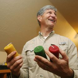 Veldon Sorensen holds some candles he has made from his beeswax at his home in Salt Lake City on Sept. 13. Sorensen is retired from Bayer but still consults for the company and others about bees.