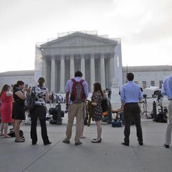 This June 24, 2013 file photo shows people waiting outside the Supreme Court in Washington.