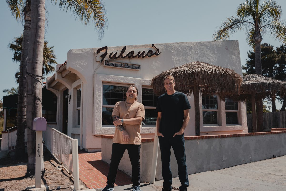 Chef Andrew Bachelier and Tony Hawk stand in front of white building with a Fulano's restaurant sign that has thatched umbrellas on the patio.