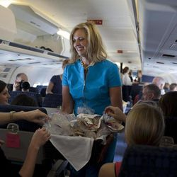 Ann Romney, wife of Republican presidential candidate, former Massachusetts Gov. Mitt Romney hands out Welsh cakes on the campaign plane, Saturday, Sept. 1, 2012, in Cincinnati, Ohio.