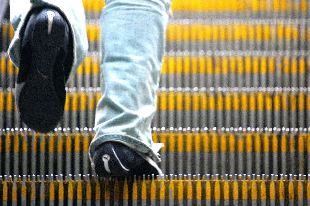 Close up of someone walking up BART escalator.