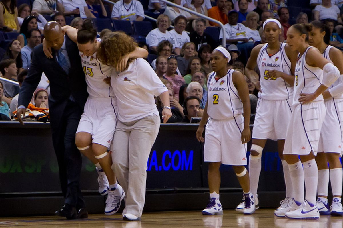 Penny Taylor being helped off the court after spraining her right ankle. (Photo by Ryan Malone)