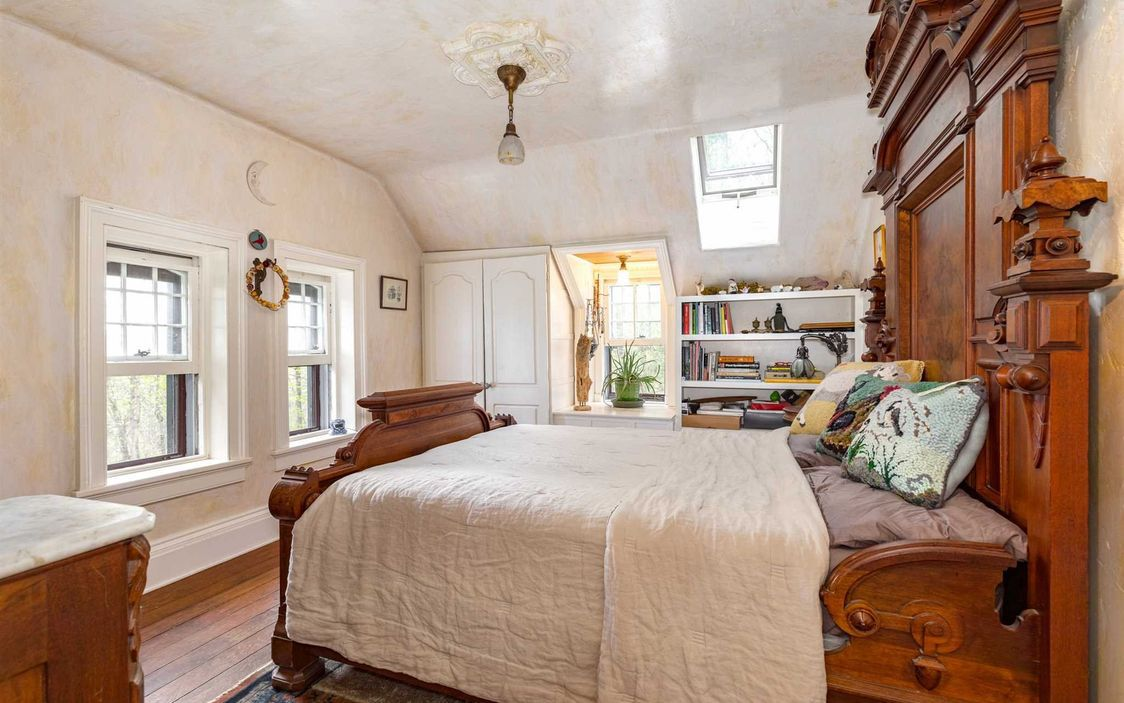 A large wooden bed sits in an upstairs bedroom with a white comforter and windows.