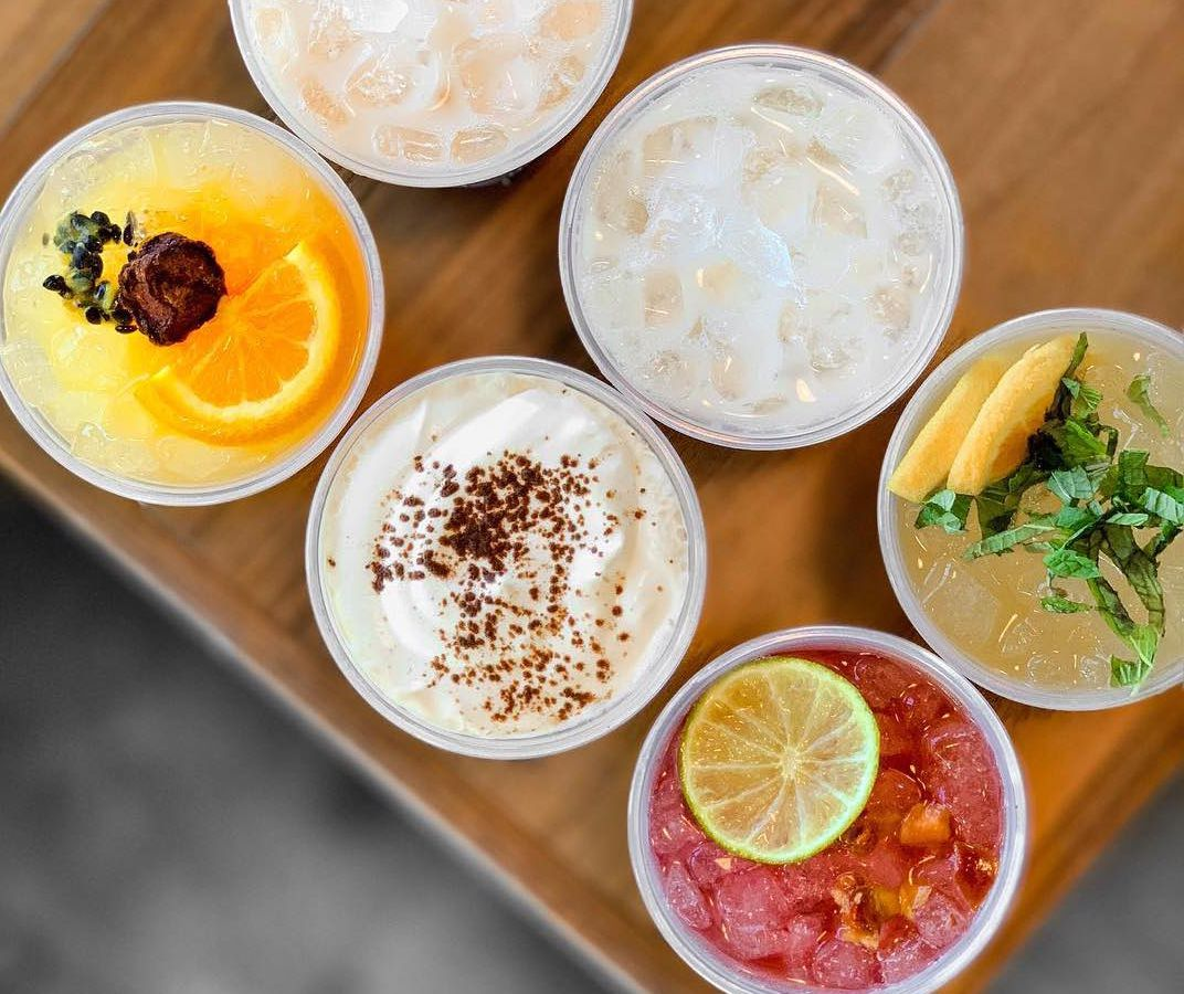 A tray of boba teas garnished with citrus, chocolate, and more